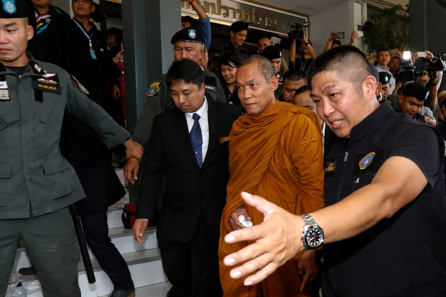 Officers escort Phra Buddha Issara, 62, an activist monk, at the Thai Police Crime Suppression Division headquarters in Bangkok on May 24 (Reuters)