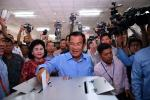 Cambodia's Prime Minister Hun Sen (C) casts his vote during the general elections as his wife Bun Rany (centre L) looks on in Phnom Penh on July 29, 2018. (MANAN VATSYAYANA/AFP/Getty Images)